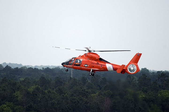 Coast Guard helicopter flying over an Alabama forest